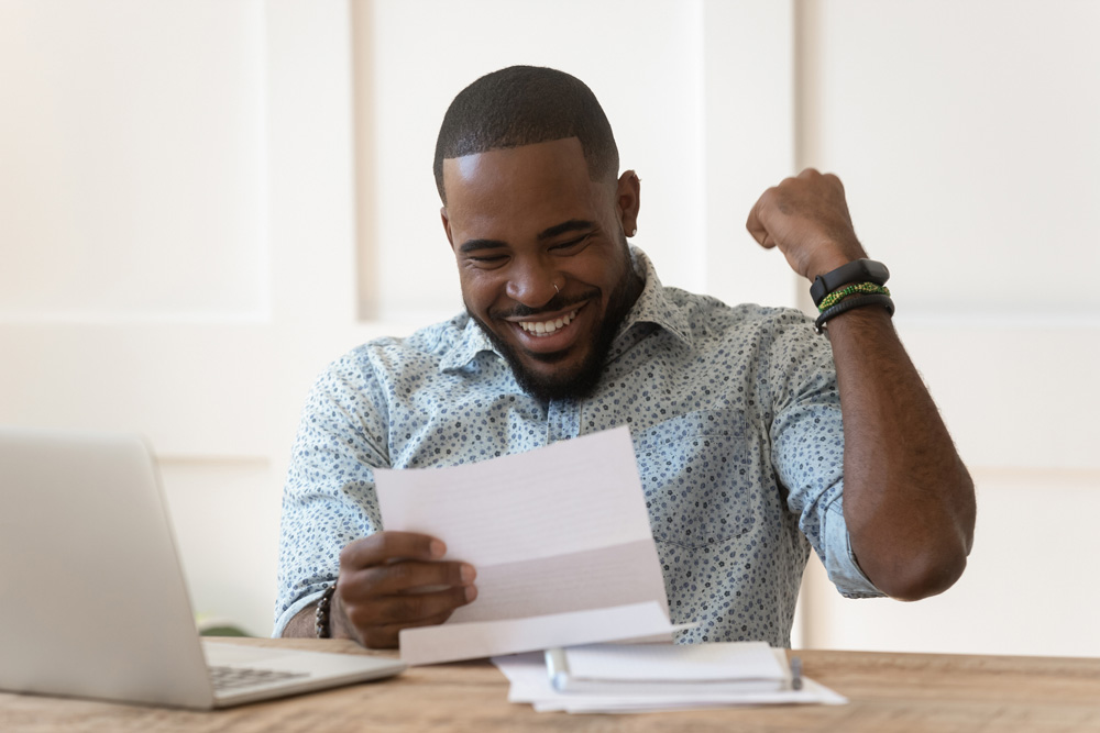 Happy man pumping fist looking at paper