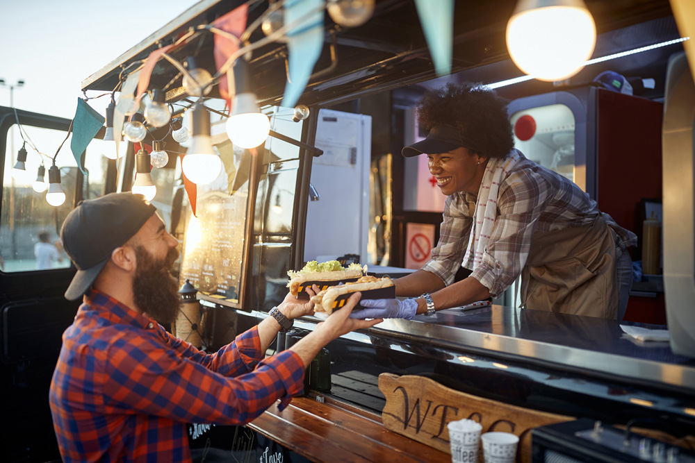 man taking food from woman inside of a food truck